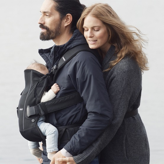 be356ea3c79 A father carrying baby using a Black Mesh BabyBjorn Baby Carrier One Air  with the mom