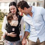 Mom carrying a baby using Ergobaby Original Carrier black/camel with dad talking to the baby beside them