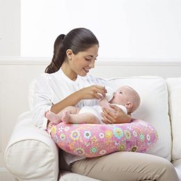 A mother sitting on a sofa while bottle feeding her baby with the help of a Chicco Boppy Nursing Pillow Wild Flowers design