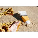 A 150g tube pack of Wotnot Natural Sunscreen 30 SPF and 2 piece orange bikini lying on the sand