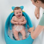 A mother bathing baby using Skip Hop Moby Smart Sling™ 3-Stage Baby Tub in Stage 3/Sitters setup