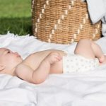 Baby Wearing Taylor/Stars aden + anais Super Soft Disposable Diaper While Lying on the Blanket
